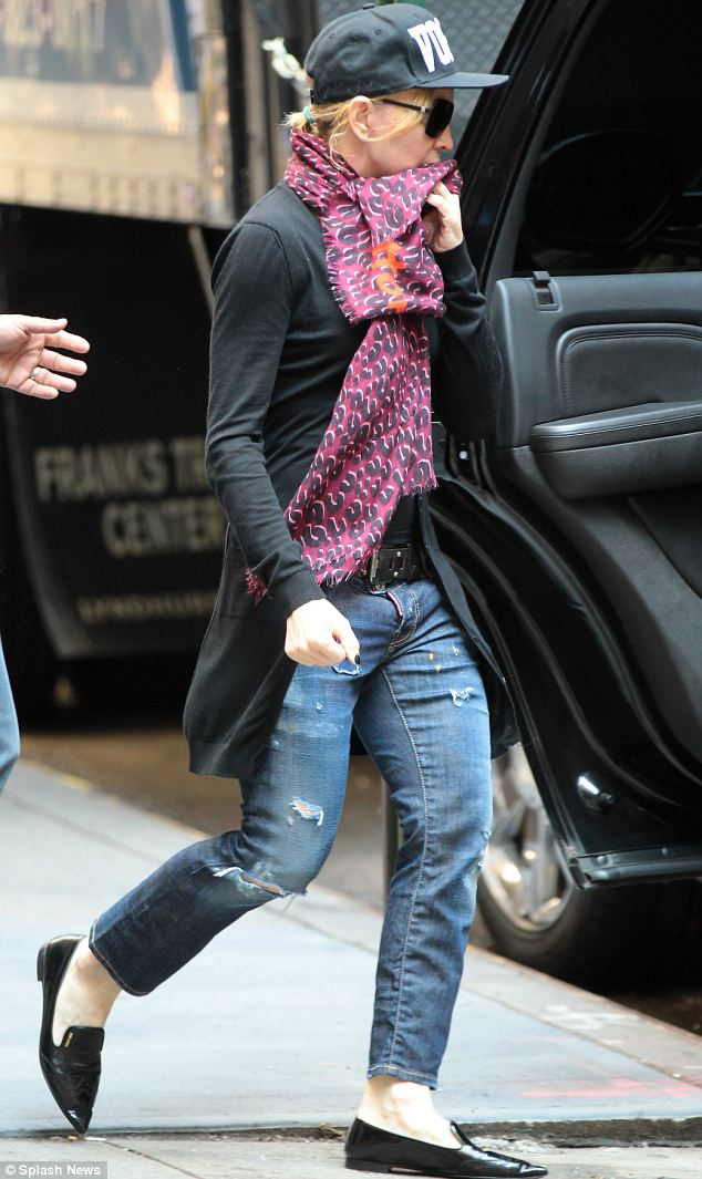 Scruffy: Madonna wore a pair of low key ripped jeans and a leopard print scarf as well as hat reading Vogue