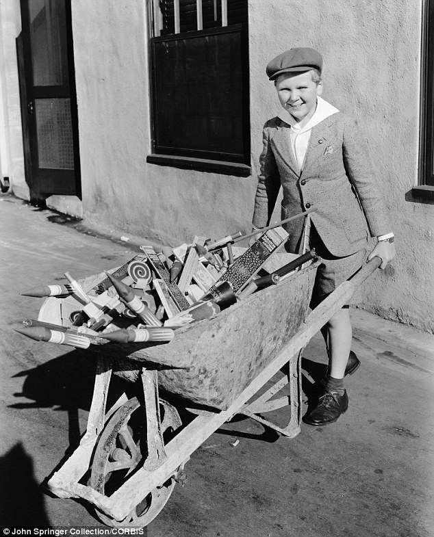 Having a blast: Child actor Jackie Cooper loads up on fireworks for a July 4 party in the 1930s