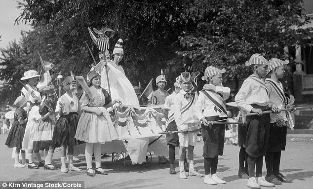 On parade: Children take part in a festival through the streets of their hometown in 1919