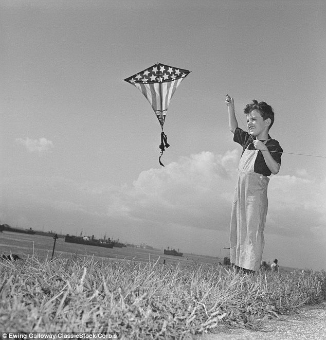 Freedom: This boy breaks into a huge grin as he flies his American flag themed kite at the water's edge