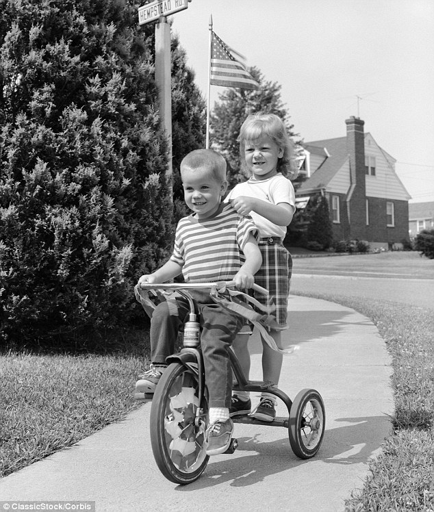 Off to the party: This little girl hitches a lift on her friend's tricycle as they ride around their block in 1963