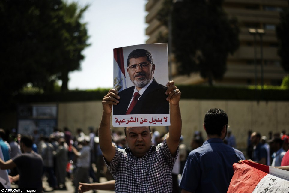 A Morsi supporter of the Muslim Brotherhood holds a picture bearing the slogan 'No alternative for the legitimacy' during a protest near Cairo University
