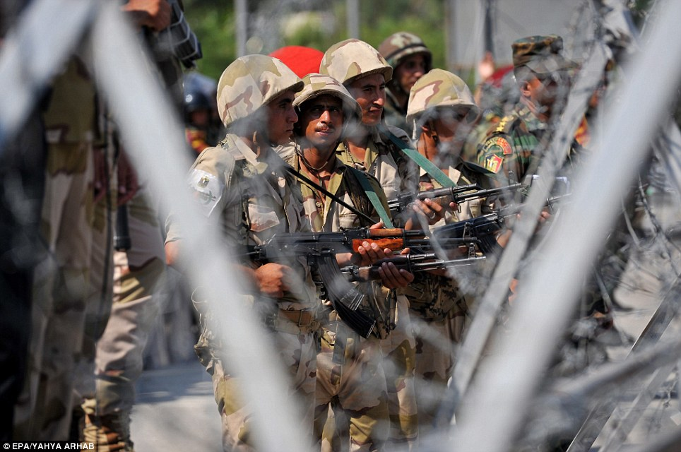 Egyptian Republican Guards forces stand guard behind barbed wire outside the headquarters of the Republican Guard. At least six have been killed