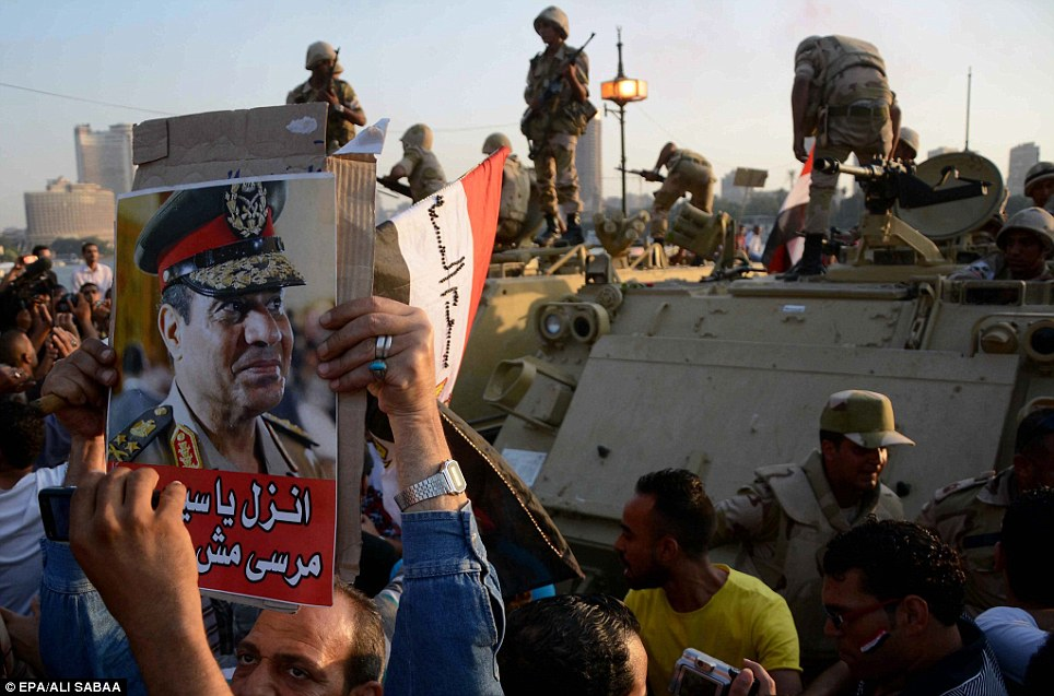Opponents of ousted President Morsi holding a poster depicting Defense Minister Abdel-Fattah Al-Sissi