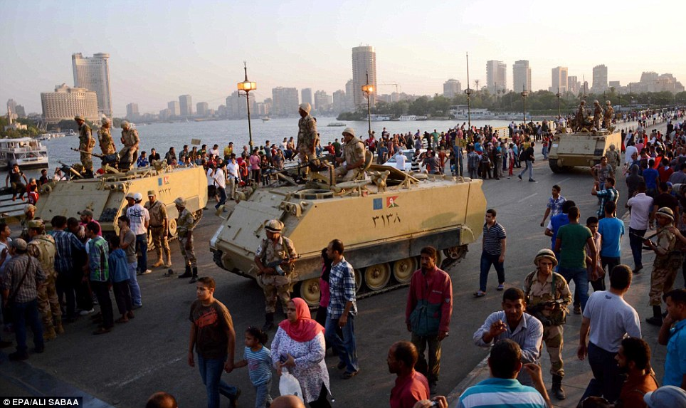 Egyptian opponents of ousted President Morsi surround an armoured vehicle on a bridge leading to Tahrir Square this evening