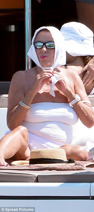 Safe in the sun: Joan made sure that she was properly protected from the blazing sun, tying back her hair and covering her face with sunglasses
