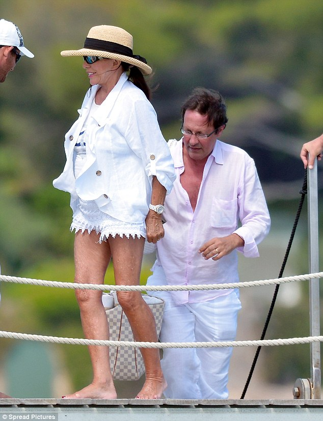 Living the life: Joan Collins looked chic in white as she boarded her yacht in Saint-Tropez on Wednesday with husband Percy