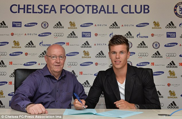 Welcome: Van Ginkel signs his contract with club secretary/director David Barnard at Cobham