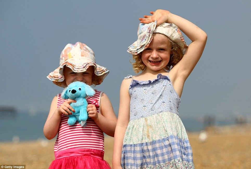 Fun in the sun: Imogen Perry, 5, and Natasha Perry, 3, enjoy the sunshine on Brighton Beach today