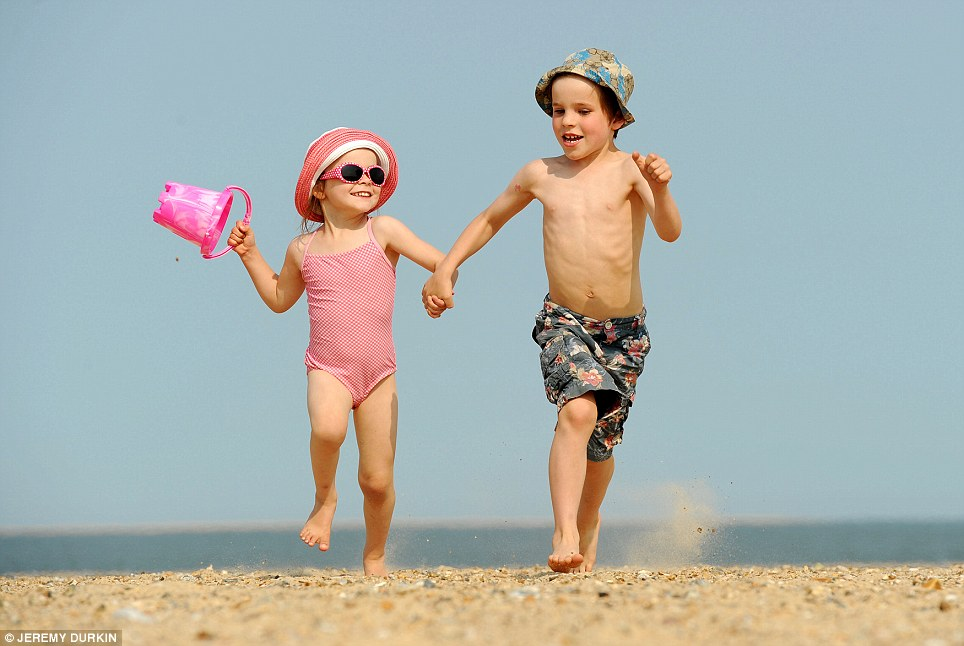 Beach dash: Genevieve and her brother Roan run across the pebbles at Great Yarmouth beach as temperatures peaked