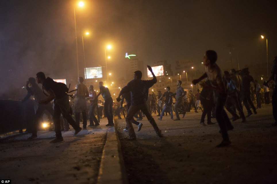 Rage: Opponents of the ousted president clashed with Muslim Brotherhood supporters near Tahrir Square in Cairo, Egypt, overnight