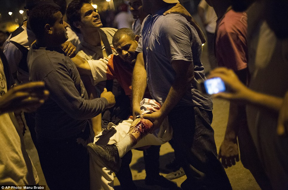 Egyptians photograph the injured leg of a demonstrator this evening after clashes between supporters and opponents of Morsi