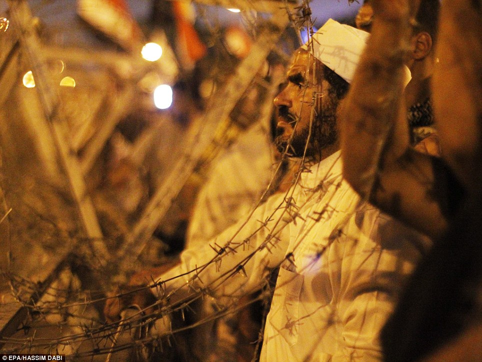 Egyptian soldiers face protesters supporting former President Morsi still gathered near the Republican Guards Headquarter in Cairo