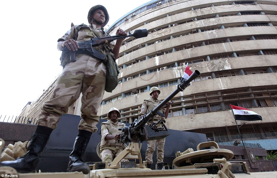 Standing guard: Soldiers are seen standing on an armoured personnel carrier postioned outside Cairo's state-run television station in Egypt today
