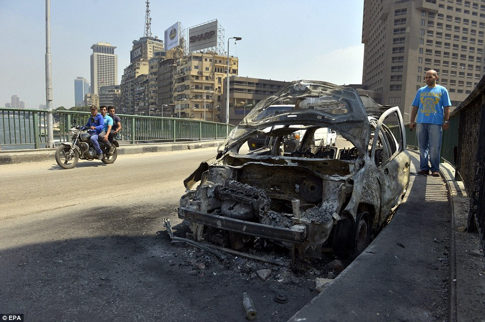 Charred remains: Egyptians drive past a car that was destroyed as Morsi's supporters clashed with his opponents in Cairo's emblematic Tahrir Square