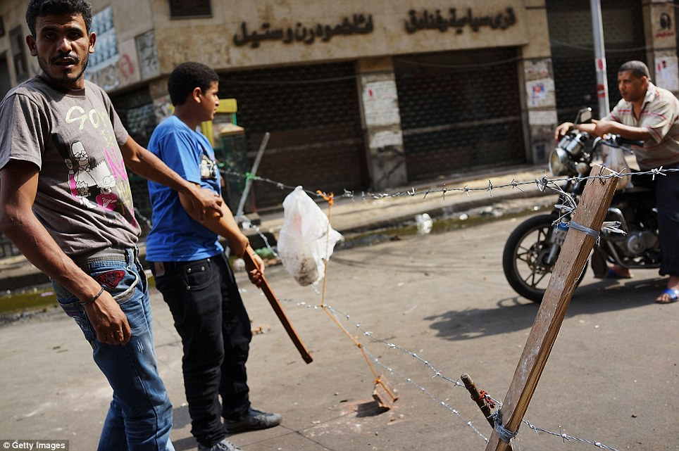 Road block: Lines of razor wire were set up across a street in Tahrir Square following a night of violence that left a reported 36 dead across Egypt and more than 1,000 people injured