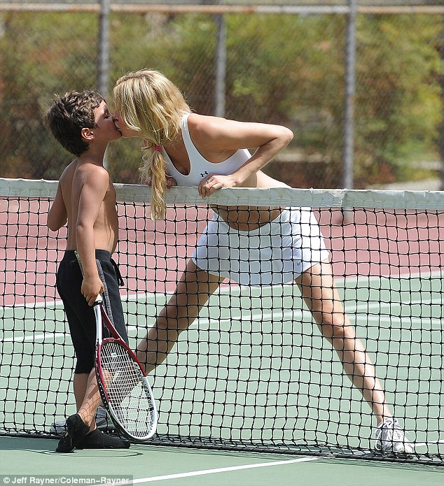 PDA: The leggy mother-of-two's tennis partner was six-year-old Jake, who took turns playing with Brandi's red-tinged racket