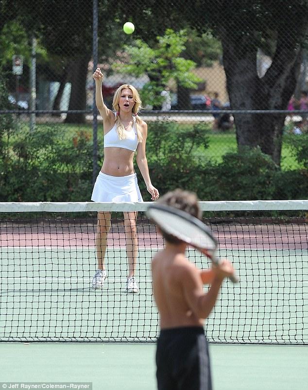 One racket, two players: Brandi tossed a ball towards Jake who held the racket like a baseball bat