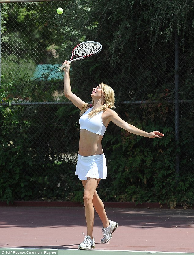Overhand: The 40-year-old reality star topped her white mini-skirt with a white sports bra and matching trainers