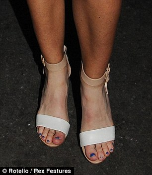 Fashion faux pas: Laura's choice of foxy footwear inadvertently showed off her dodgy tennis tan