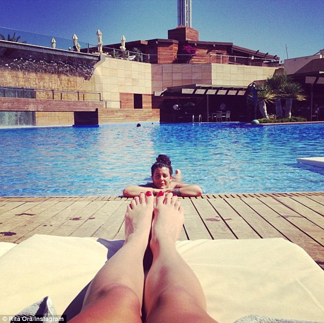 Picture perfect: Rita posted a snap of her feet as she chilled out in the sunshine by her hotel pool