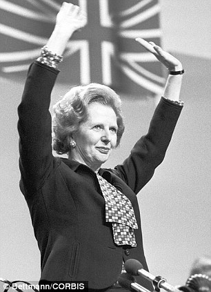 Prime Minister Margaret Thatcher stands with her arms raised at a Conservative Party conference in Brighton