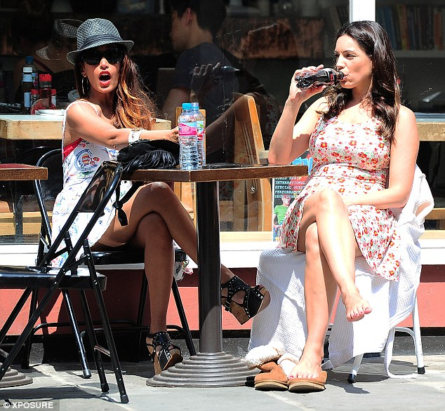 Cooling down: Kelly airs her feet as she and Preeya relax over their drinks at a nearby cafe