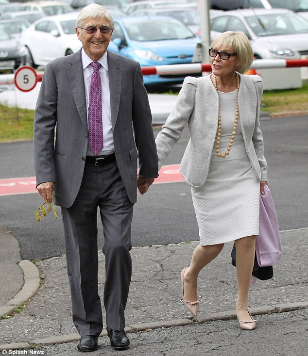 Veteran broadcaster Sir Michael Parkinson - pictured here at Wimbledon with wife Mary - has revealed he is battling prostate cancer