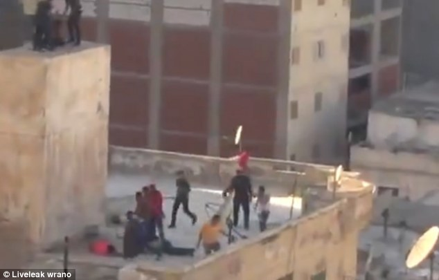 Fatal: The second boy, in red, is brought off the ledge and shortly before the camera moves away, the aggressive Islamist mob can be seen beating the teenagers, one of which reportedly died