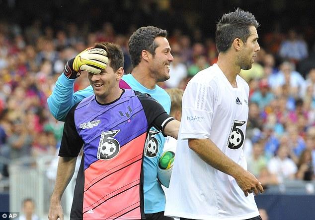 Hands on: Julio Cesar shares a joke with Messi as former Fulham defender Carlos Bocanegra stands on