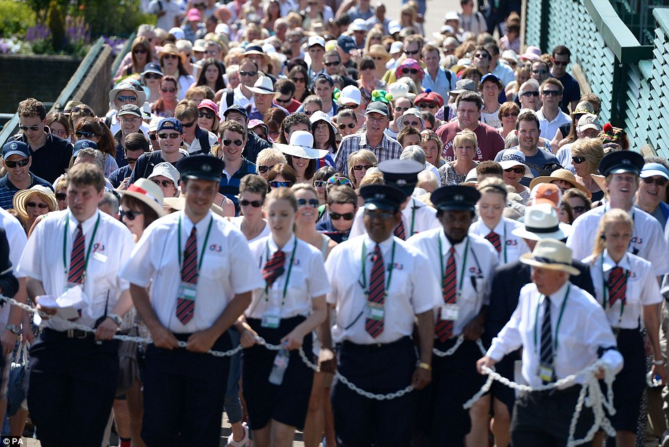 Crowd control: Thousands of fans are walked to Murray Mount at The All England Lawn Tennis and Croquet Club in Wimbledon ahead of yesterday's final