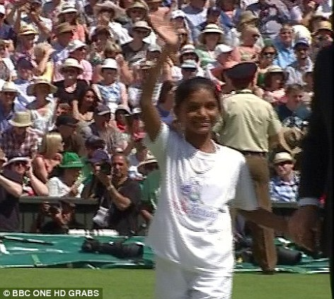 Special honour: Pinki waves and smiles at the crowd as she walks on to Centre Court at Wimbledon to help perform the coin toss