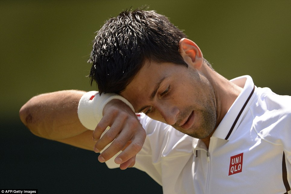 Under pressure: Novak Djokovic wipes his brow between points during his men's final match against Andy Murray