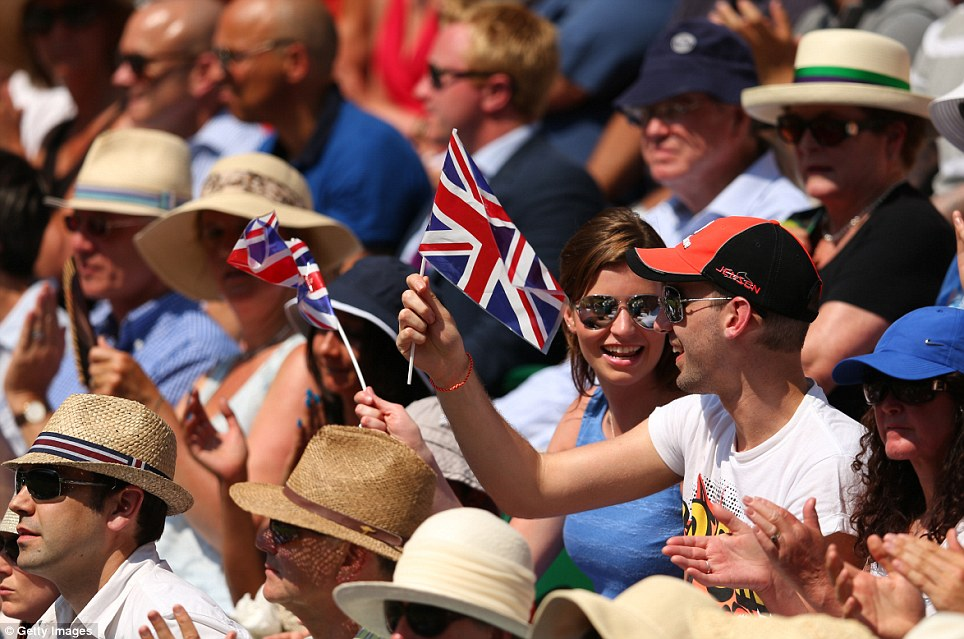 Coveted seats: Spectators wave Union Jack flags on Centre Court as they watch Andy Murray in the final