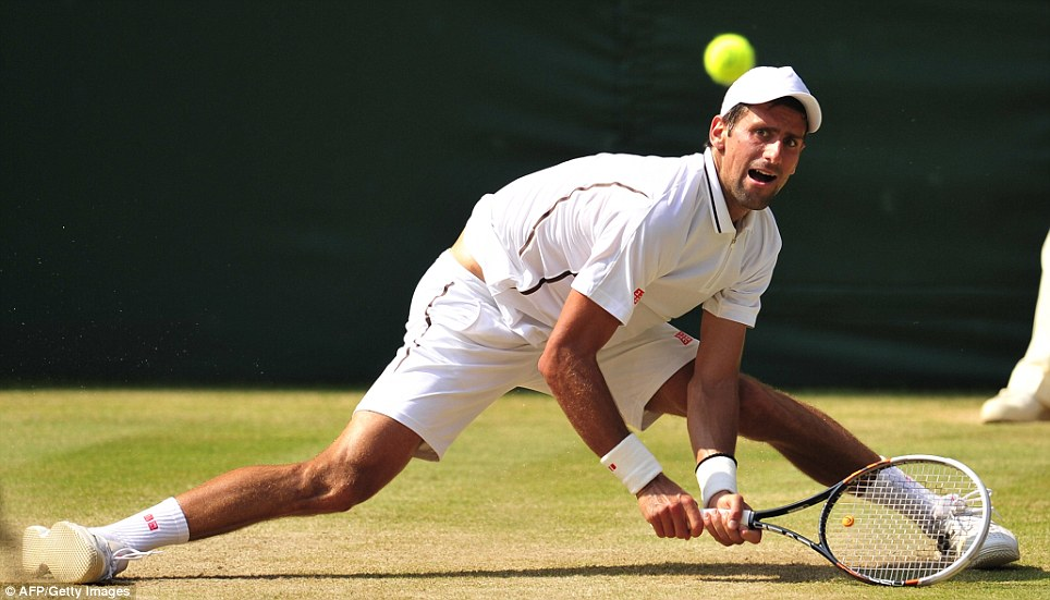 Doing the splits: Novak Djokovic manages to return a difficult shot to Andy Murray doing the men's final yesterday