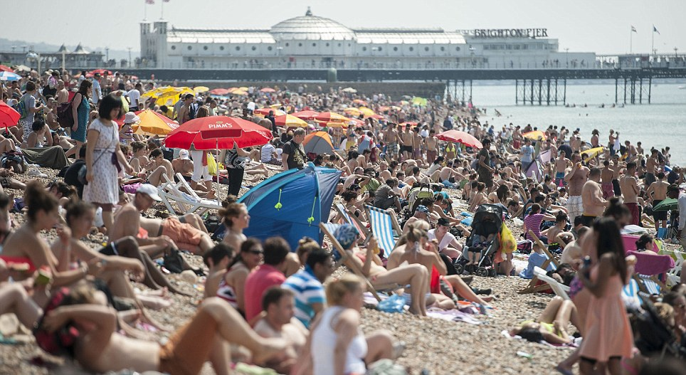 Packed: Holidaymakers get a suntan at Brighton yesterday as temperatures hit the 80s