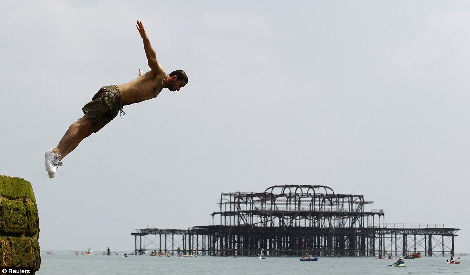 Intrepid: A man dives into the English Channel with Brighton's burned-out West Pier in the background