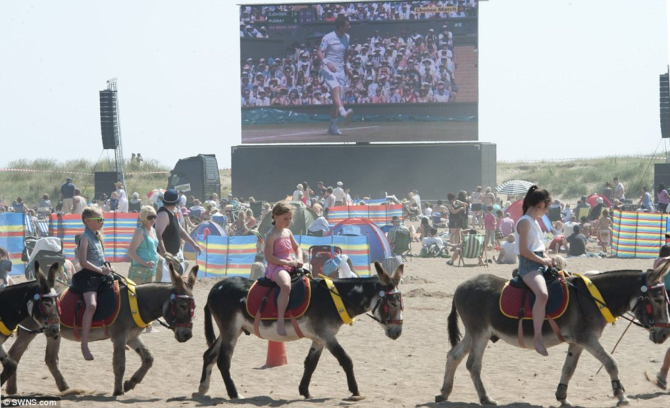 Classic summer: A group of girls on donkey pass a big screen on Skegness beach showing Andy Murray in the Wimbledon final