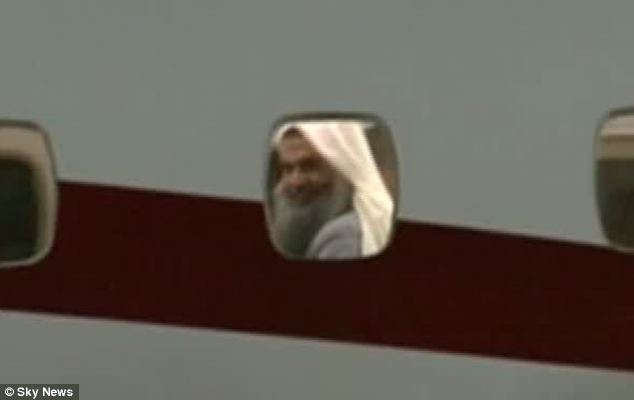 Leaving: Qatada was seen smirking from the window of the plane as it left Britain in the early hours of Sunday