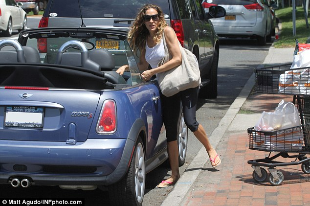 Keeping it natural: The actress wore her trademark curly hair unstyled and loose over her shoulders and appeared to go without makeup, shielding her eyes with giant sunglasses