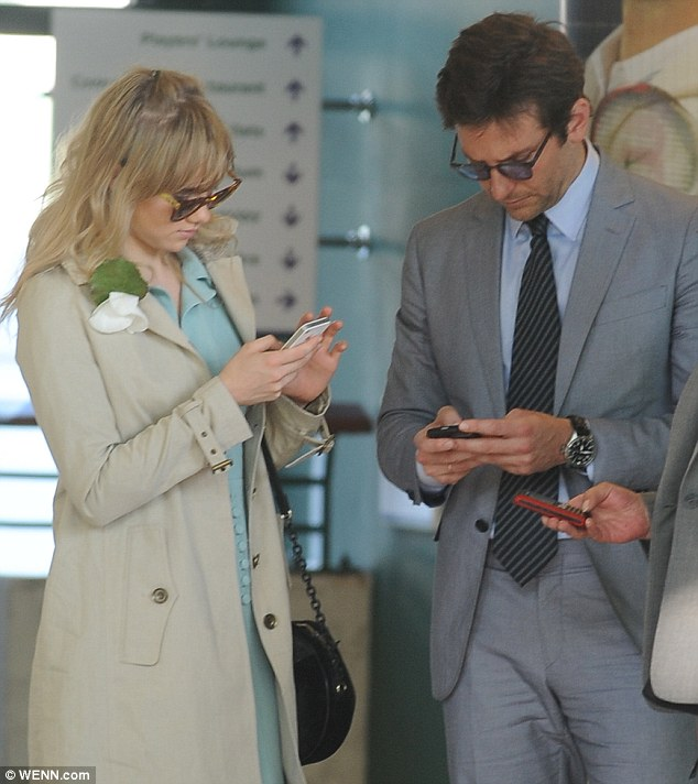 Preoccupied: Bradley Cooper and Suki Waterhouse check their messages after the Men's Final at Wimbledon on Sunday