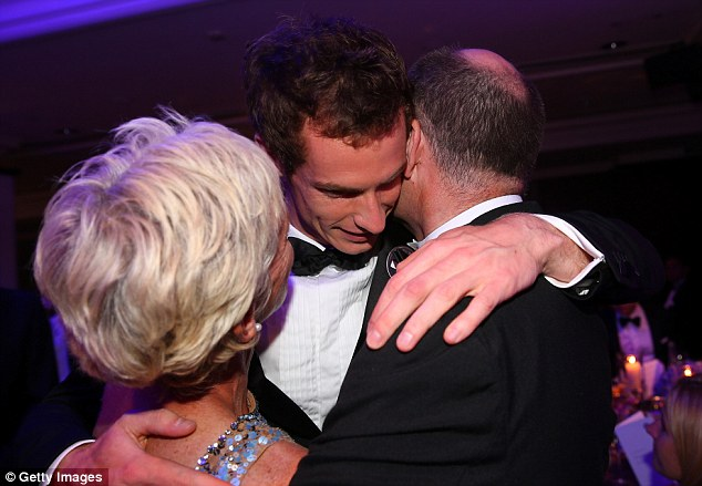 Happy families: Murray hugs his parents Judy and William as they celebrate his famous victory