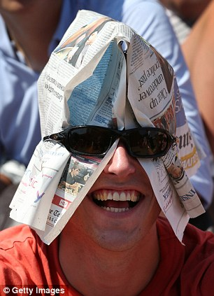 A spectator improvises some shade with a newspaper