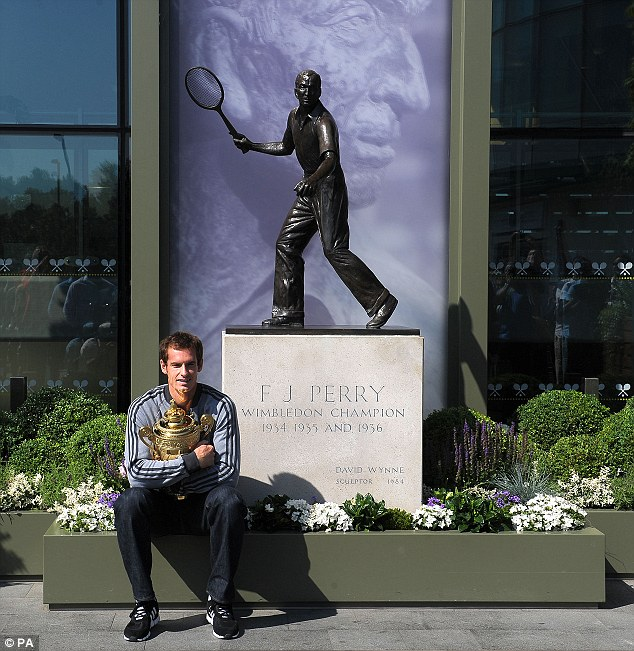 Champion: Andy Murray clutches his trophy outside Centre Court in front of a statue of Fred Perry - the last British man to win Wimbledon back in 1936