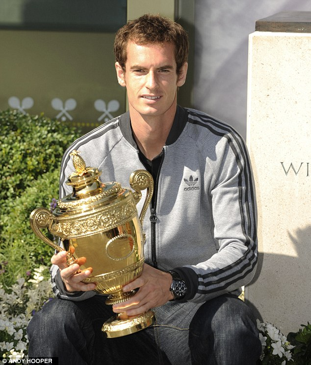 Mine, all mine: Murray keeps a close grip on the trophy after breaking the 77-year British hoodoo at Wimbledon