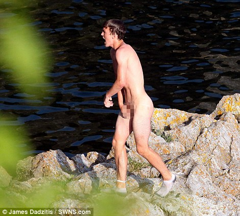 A young naked man gets out of the water after jumping off a 65ft wall at 'Dead Man's Cove'