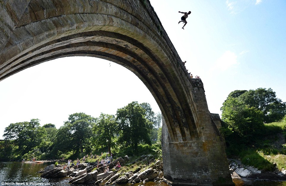 The current heatwave is attracting dare devil 'Tombstoners' defying warning signs not to jump from Devils Bridge in Kirkby Lonsdale