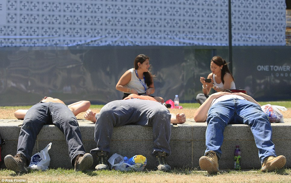 Workmen make the most of the heat by grabbing a quick snooze on their lunch break in Tower Hill