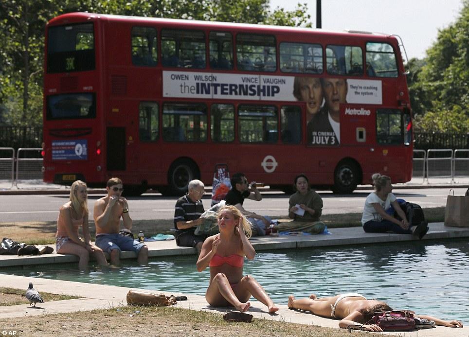 People enjoy the sun near a fountain at Hyde Park in London