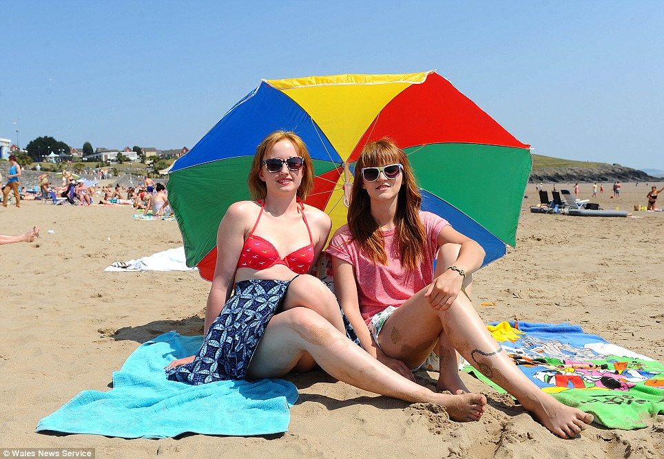 Graduates Hayley Ryan (left) and Jenny Griffiths (right) enjoy the sun in the heatwave on Barry Island Beach